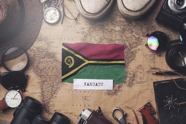 Drapeau du vanuatu entre les accessoires du voyageur sur l'ancienne carte vintage. tir aérien