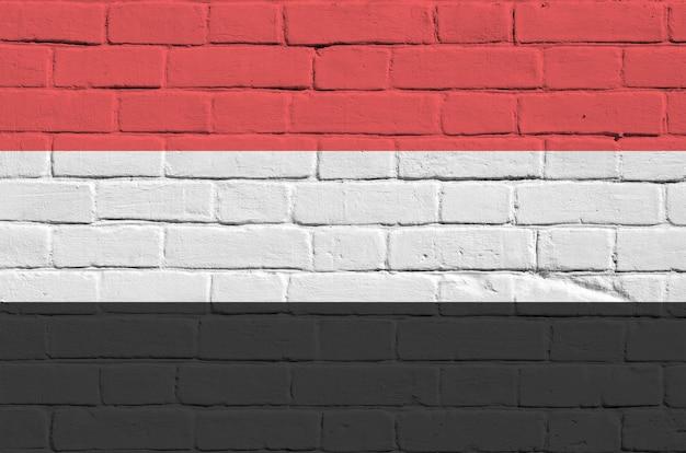 Drapeau du yémen dans les couleurs de peinture sur le vieux mur de briques