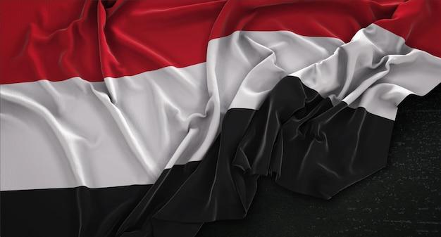 Drapeau du yémen enroulé sur fond sombre 3d render