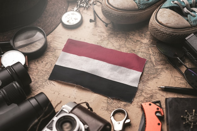 Drapeau du yémen entre les accessoires du voyageur sur l'ancienne carte vintage. concept de destination touristique.