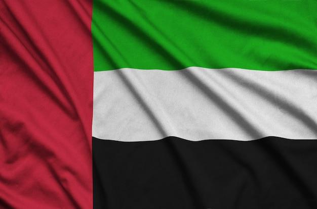 Le drapeau des émirats arabes unis est représenté sur un tissu de sport avec de nombreux plis.