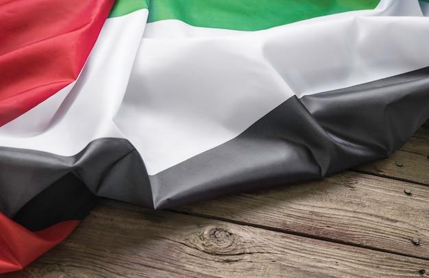 Le drapeau des emirats arabes unis se trouve sur un fond en bois marron avec un espace pour le texte ou l'image