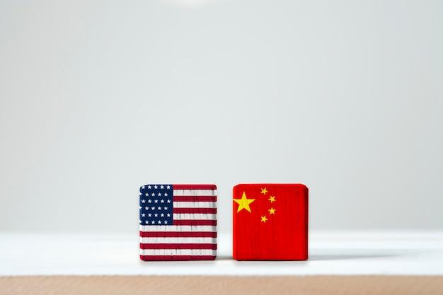 Drapeau des états-unis et drapeau de la chine avec écran d'impression sur cubes en bois. symbole de la barrière fiscale entre les états-unis d'amérique et la chine