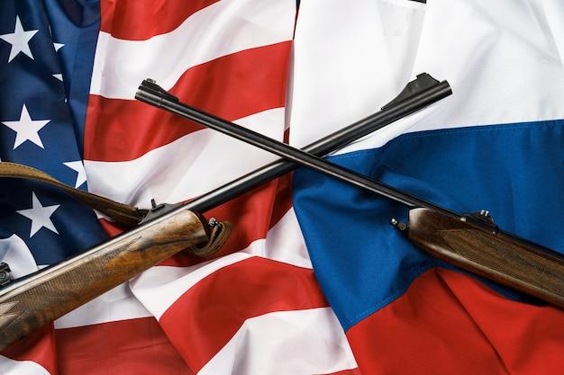 Drapeau des etats-unis et fond de drapeau de la russie avec deux fusils de chasse croisés