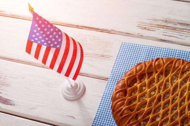Drapeau des états-unis, tarte et serviette. tarte portant à côté du drapeau de la table. petit déjeuner de vrai patriote. tarte sucrée traditionnelle aux pommes.
