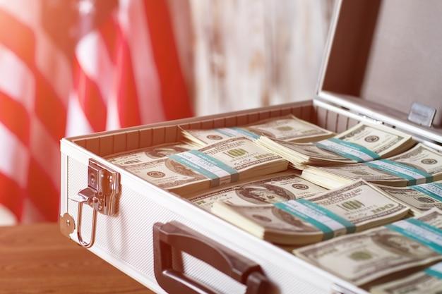 Drapeau et étui avec de l'argent. paquets de dollars près du drapeau américain. affaires dans un grand pays. la richesse vous attend.