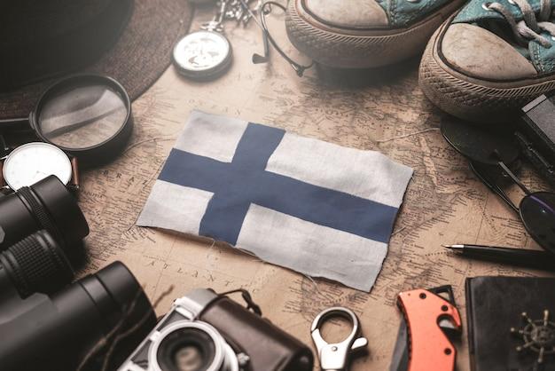Drapeau de la finlande entre les accessoires du voyageur sur l'ancienne carte vintage. concept de destination touristique.