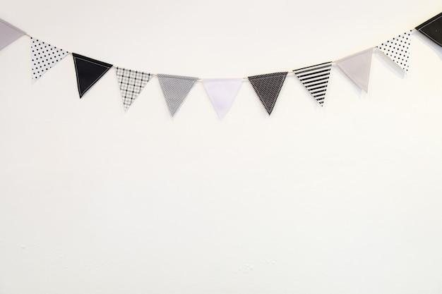 Drapeau de forme de petit triangle blanc noir suspendu courbe vers le bas du mur de plâtre