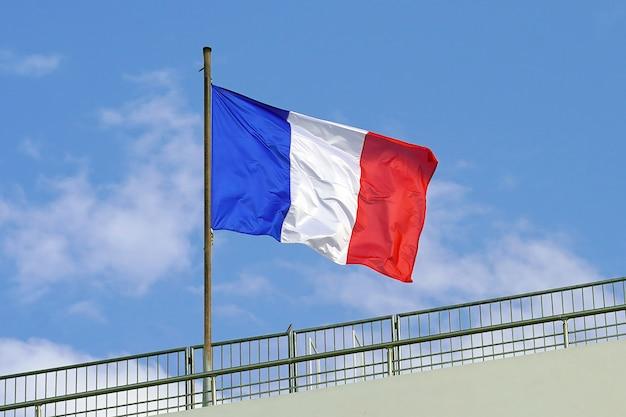 Drapeau français sur fond de ciel bleu.