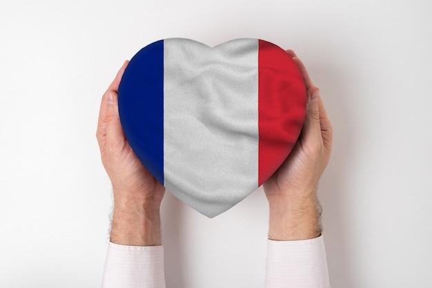 Drapeau de la france sur une boîte en forme de coeur dans une main masculine.