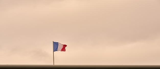 Drapeau de la france avec un ciel gris en arrière-plan.