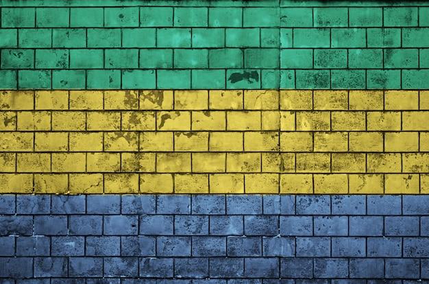Le drapeau gabonais est peint sur un vieux mur de briques