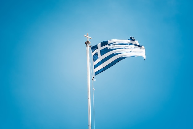 Drapeau grec agitant contre le ciel bleu