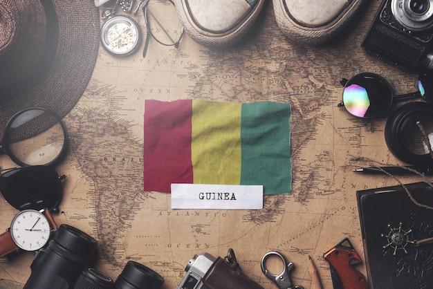 Drapeau de la guinée entre les accessoires du voyageur sur l'ancienne carte vintage. tir aérien