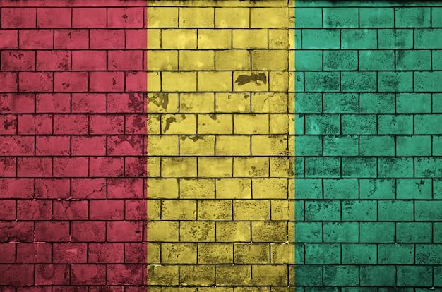 Le drapeau de la guinée est peint sur un vieux mur de briques