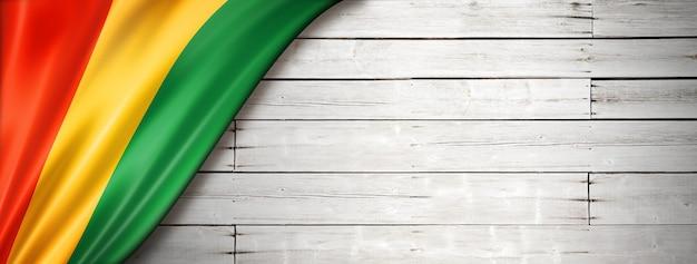 Drapeau de la guinée sur le vieux mur blanc. bannière panoramique horizontale.