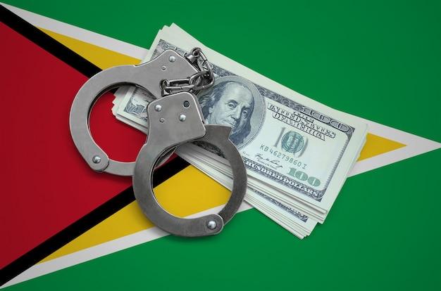 Drapeau guyanais avec des menottes et un paquet de dollars. la corruption monétaire dans le pays. crimes financiers