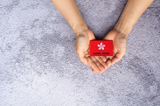 Drapeau de hong kong dans sa main. concept d'amour, de soins, de protection et de sécurité.