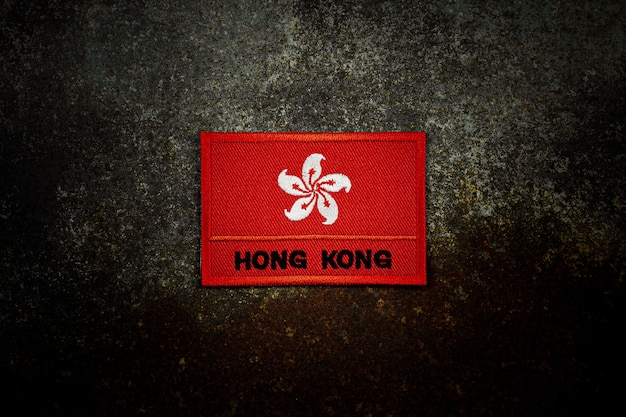 Drapeau de hong kong sur le sol en métal rouillé abandonné dans le noir.