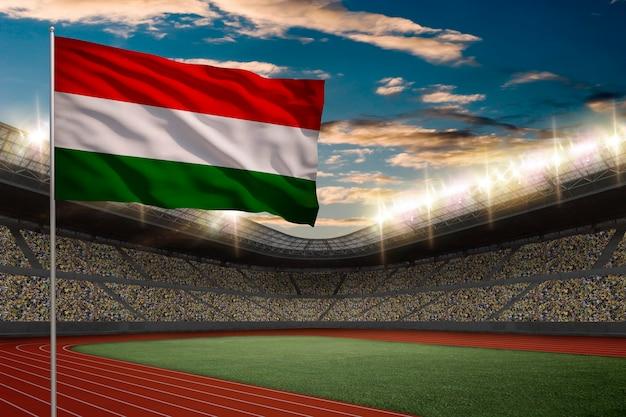 Drapeau hongrois devant un stade d'athlétisme avec des fans.