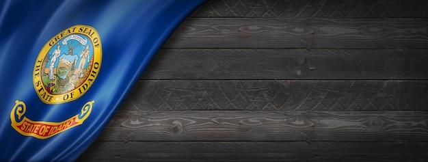 Drapeau de l'idaho sur la bannière de mur en bois noir, usa. illustration 3d