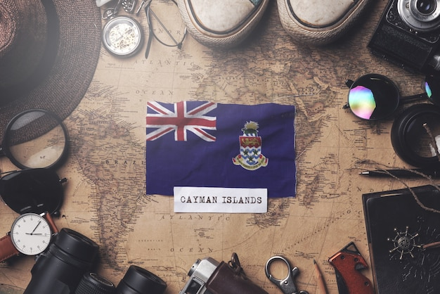 Drapeau des îles caïmans entre les accessoires du voyageur sur l'ancienne carte vintage. tir aérien