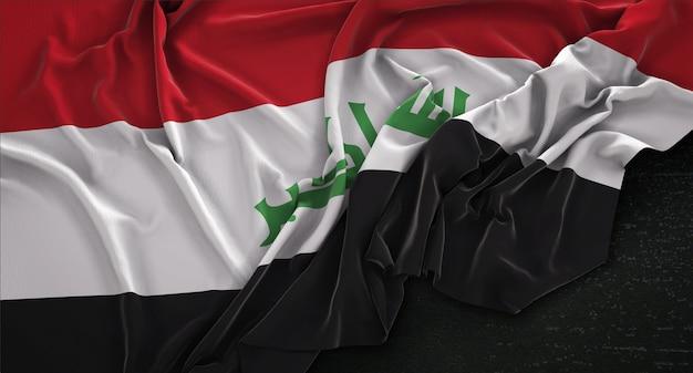 Drapeau de l'irak enroulé sur fond sombre 3d render