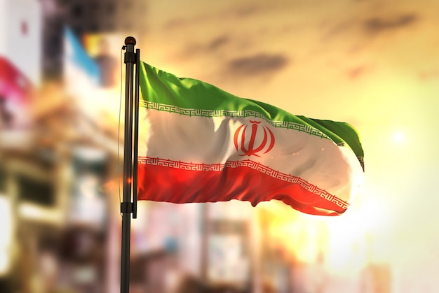 Drapeau iranien contre la ville fond flou au lever du soleil rétro-éclairage