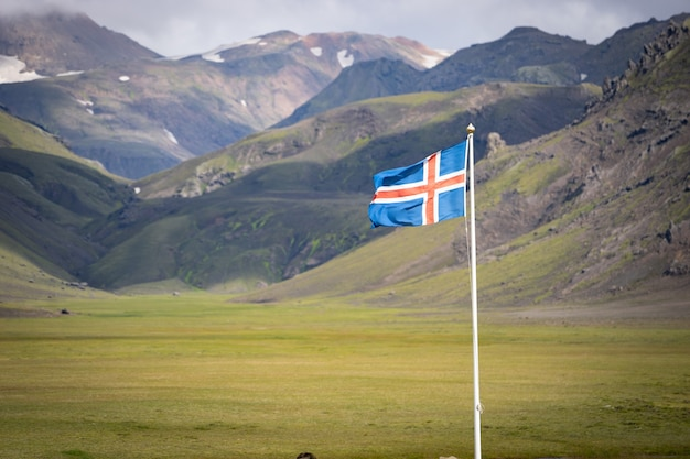 Drapeau de l'islande contre les montagnes vertes et le ciel bleu.