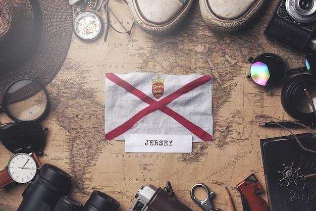 Drapeau jersey entre les accessoires du voyageur sur l'ancienne carte vintage. tir aérien