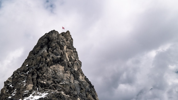 Drapeau de la lettonie au sommet d'une montagne rocheuse sous un ciel nuageux