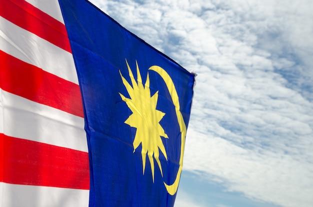 Drapeau de la malaisie sur le ciel bleu