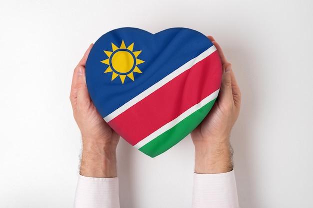 Drapeau de la namibie ali sur une boîte en forme de coeur dans une main masculine.
