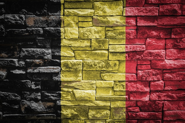 Drapeau national de la belgique sur fond de mur de pierre. bannière de drapeau sur fond de texture de pierre