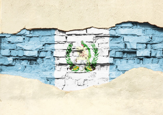 Drapeau national du guatemala sur un fond de brique. mur de briques avec plâtre partiellement détruit, arrière-plan ou texture.