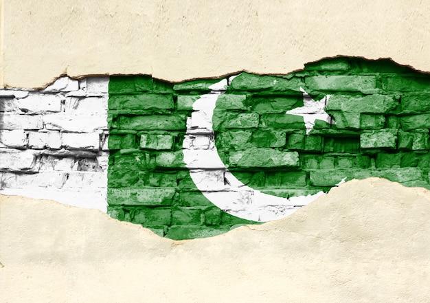 Drapeau national du pakistan sur un fond de brique. mur de briques avec plâtre partiellement détruit, arrière-plan ou texture.