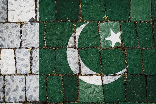 Drapeau national du pakistan sur fond de mur de pierre. bannière de drapeau sur fond de texture de pierre.