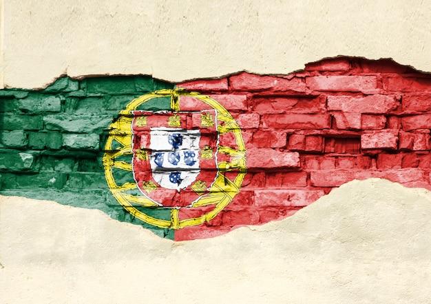 Drapeau national du portugal sur un fond de brique. mur de briques avec plâtre partiellement détruit, arrière-plan ou texture.