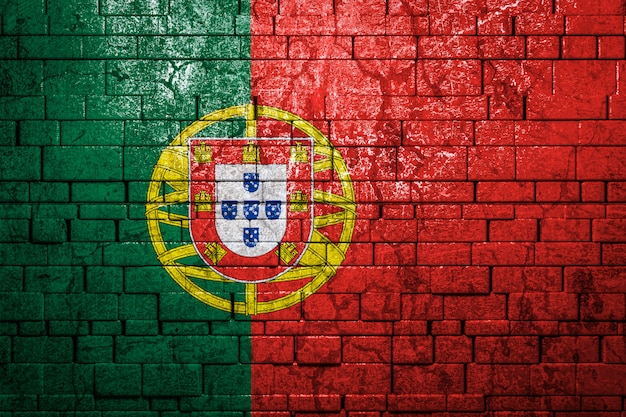 Drapeau national du portugal sur fond de mur de brique.