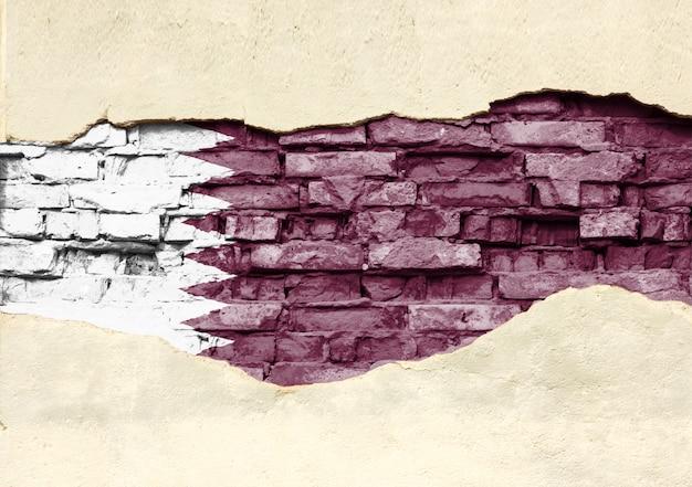 Drapeau national du qatar sur un fond de brique. mur de briques avec plâtre partiellement détruit, arrière-plan ou texture.