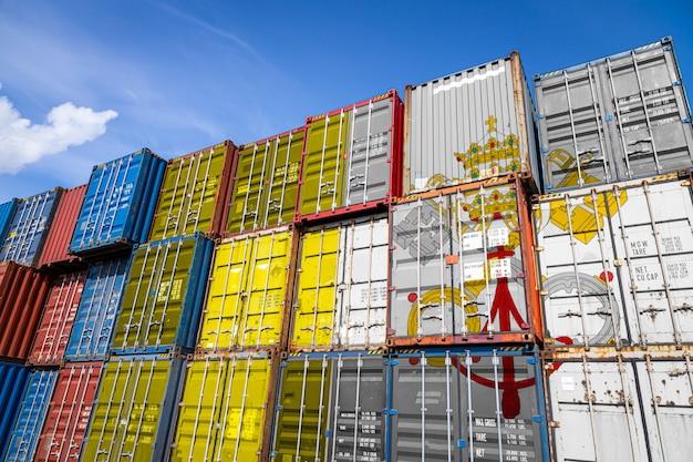 Drapeau national du vatican sur un grand nombre de conteneurs métalliques pour le stockage de marchandises empilées en rangées
