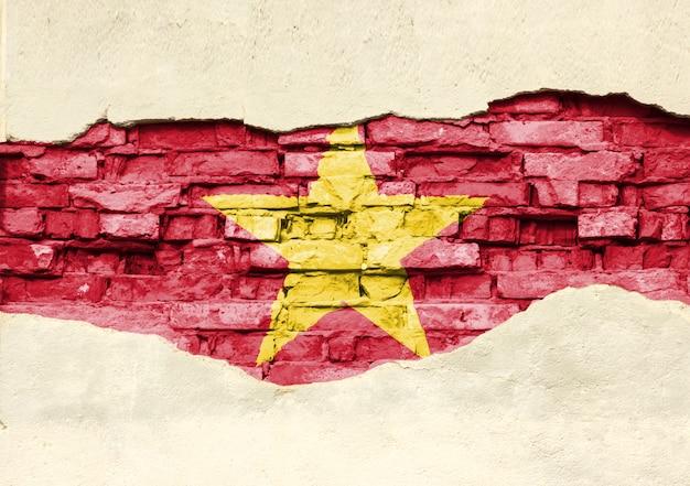Drapeau national du vietnam sur un fond de brique. mur de briques avec plâtre partiellement détruit, arrière-plan ou texture.