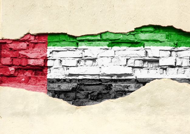Drapeau national des émirats arabes unis sur un fond de brique. mur de briques avec plâtre partiellement détruit, arrière-plan ou texture.