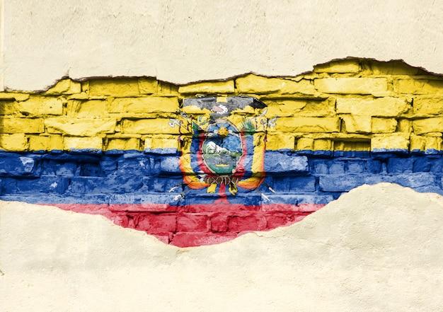 Drapeau national de l'équateur sur un fond de brique. mur de briques avec plâtre partiellement détruit, arrière-plan ou texture.