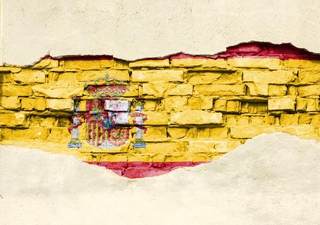 Drapeau national de l'espagne sur un fond de brique. mur de briques avec plâtre partiellement détruit, arrière-plan ou texture.