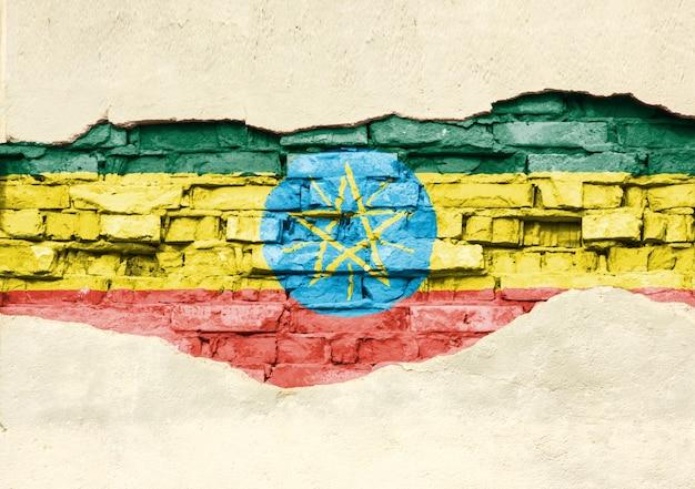 Drapeau national de l'éthiopie sur un fond de brique. mur de briques avec plâtre partiellement détruit, arrière-plan ou texture.