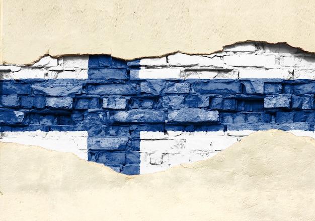 Drapeau national de la finlande sur un fond de brique. mur de briques avec plâtre partiellement détruit, arrière-plan ou texture.