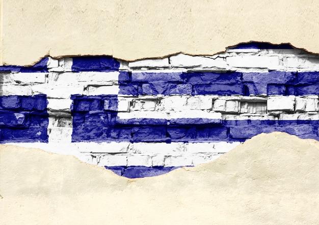 Drapeau national de la grèce sur un fond de brique. mur de briques avec plâtre partiellement détruit, arrière-plan ou texture.