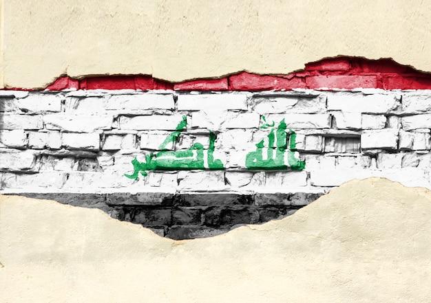 Drapeau national de l'irak sur un fond de brique. mur de briques avec plâtre partiellement détruit, arrière-plan ou texture.