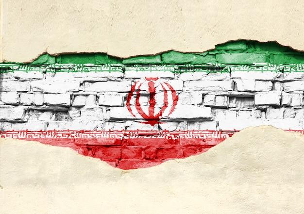 Drapeau national de l'iran sur un fond de brique. mur de briques avec plâtre partiellement détruit, arrière-plan ou texture.